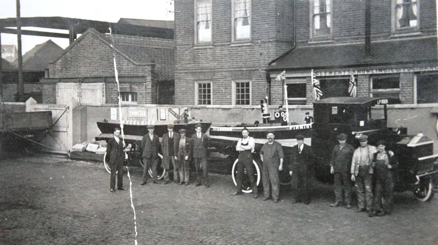 Lorry with two boats loaded, men stand in front posed for photo